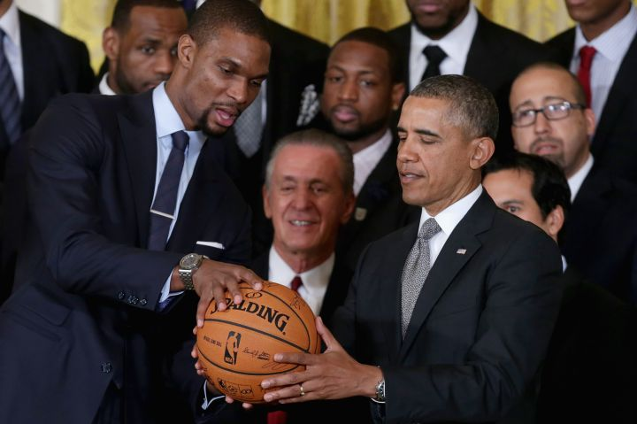 Chris Bosh hands POTUS a basketball with the signatures of the team at The Heat's visit to the White House.