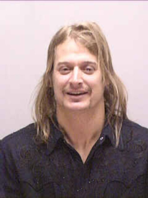 Kid Rock laughed as he was arrested by police after allegedly punching a DJ at a strip club in 2005.
