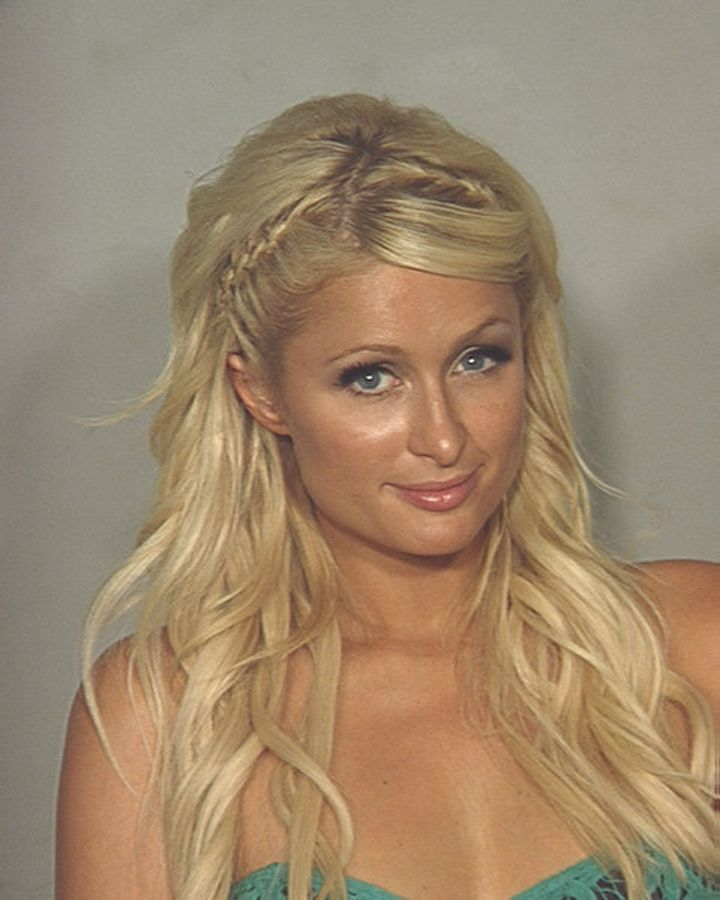 Paris Hilton smiling for her 2010 police mugshot after she was arrested in Las Vegas for allegedly possessing cocaine.