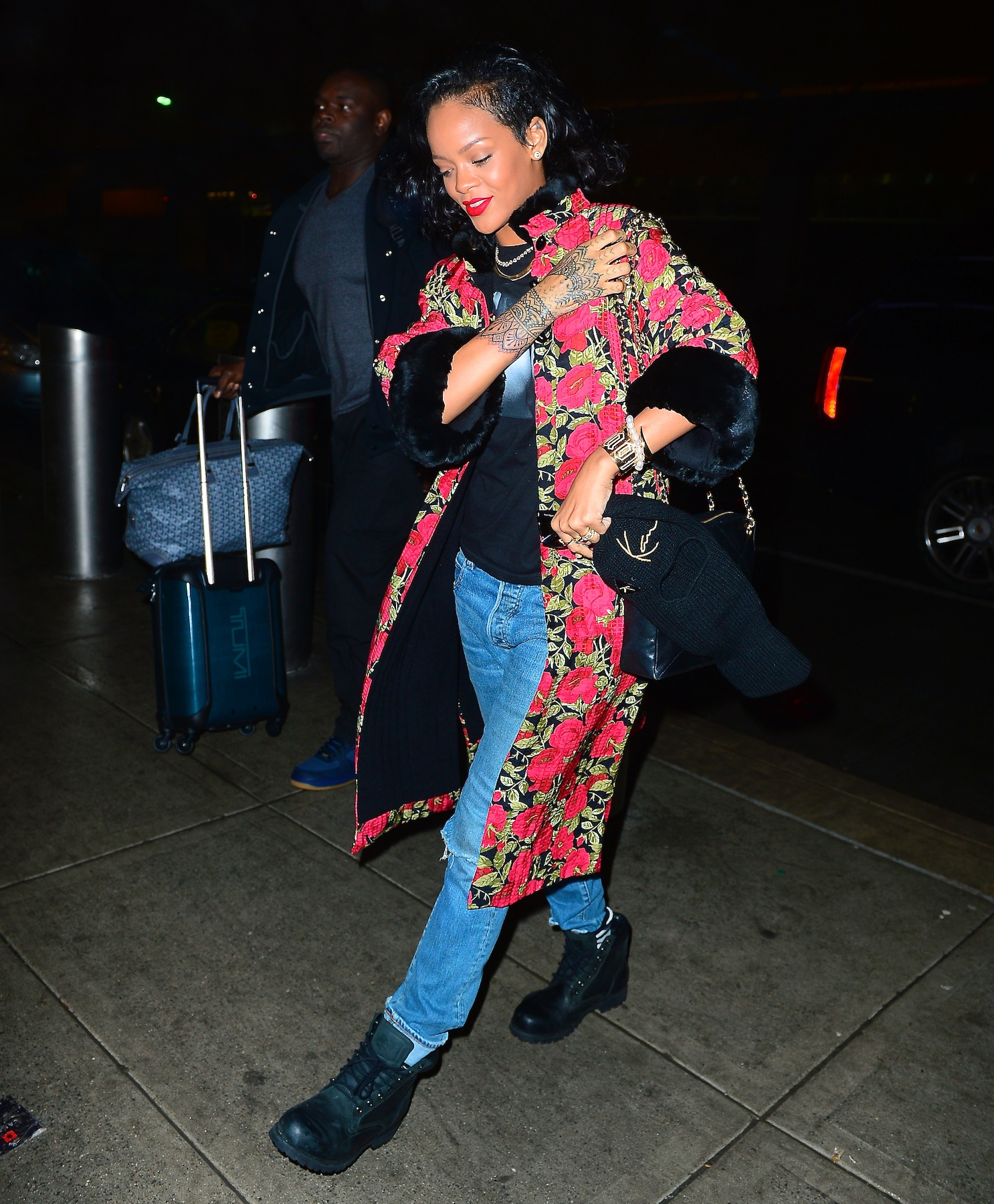 Rihanna wears a red floral overcoat as she departs for Brazil with new tattoos