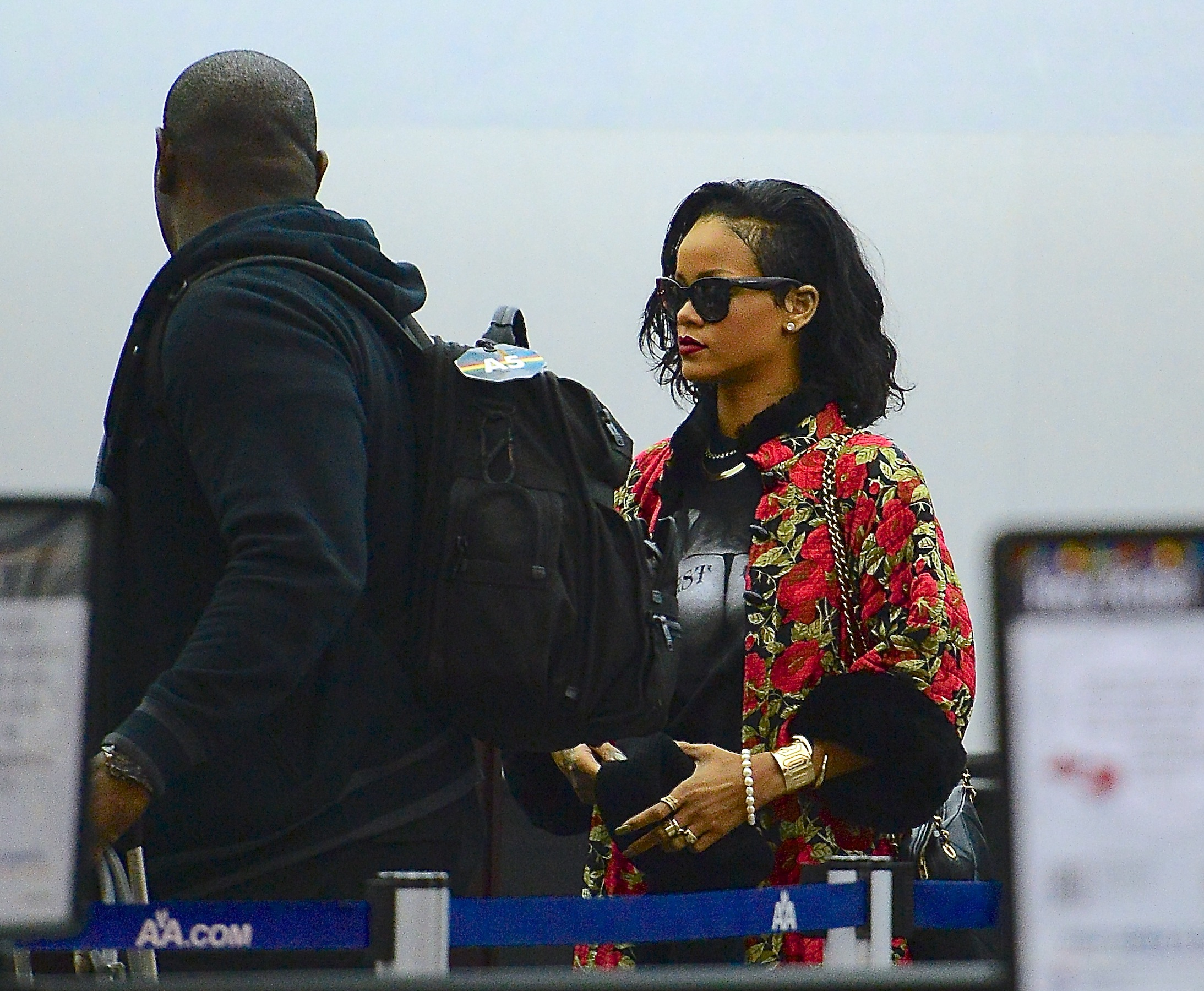 Rihanna poses with her favorite paparazzi and jokes with a robber mask at the airport