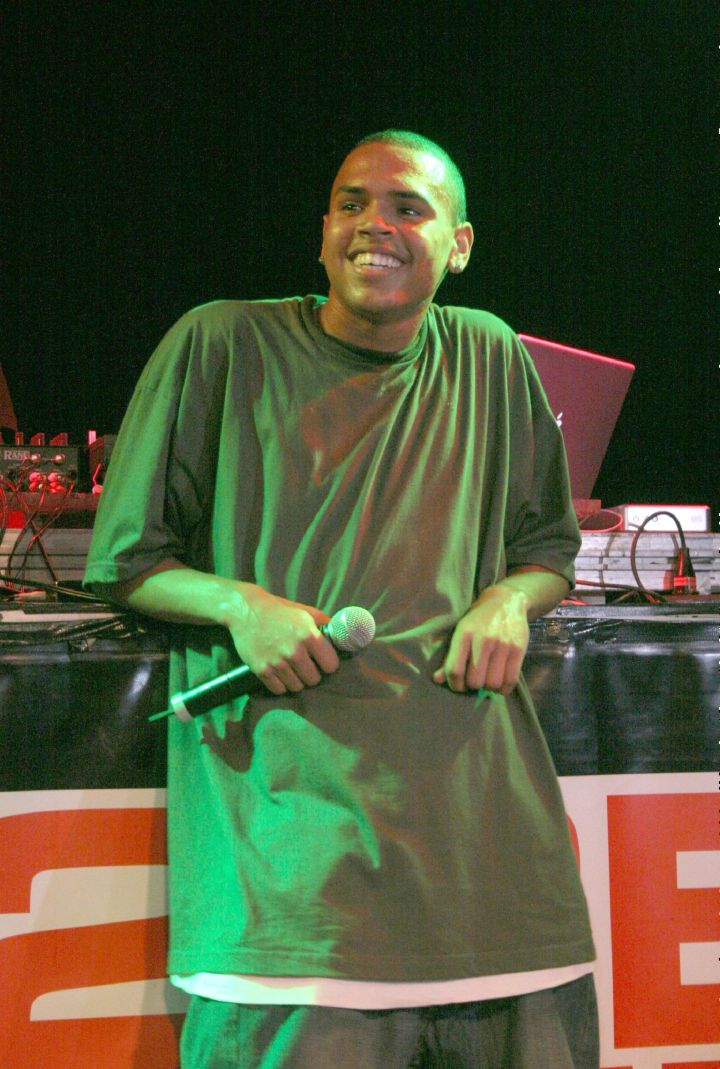 Chris Brown wears a super tall baggy t-shirt while performing with a huge smile on his face.