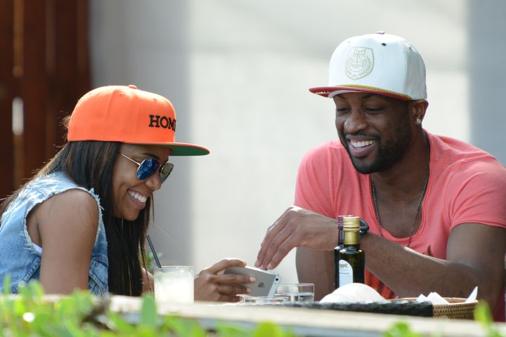 Dwyane and Gabrielle don caps while having a good time dining out.