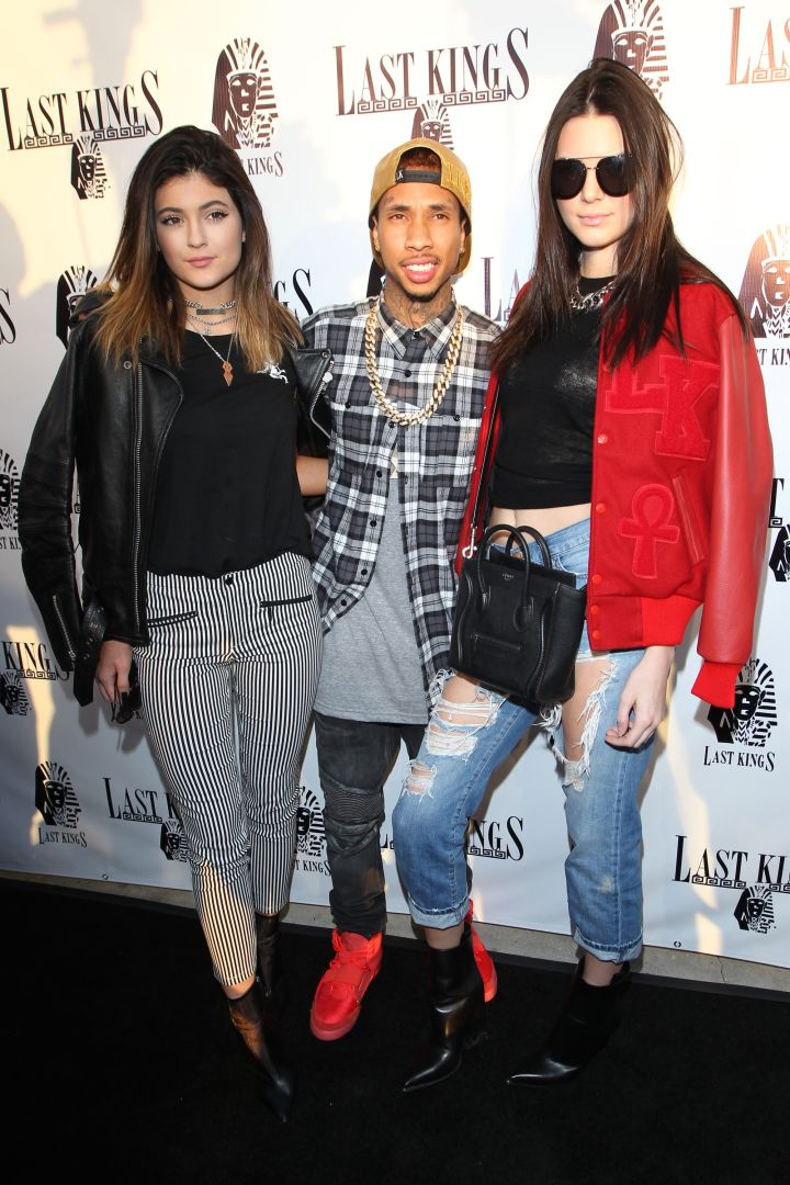 Tyga cozies up to the Jenner sisters.