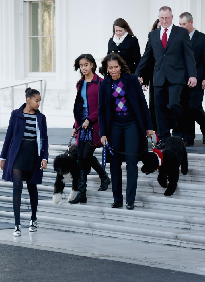 The ladies of the White House cover up in jewel-toned coats while walking Bo.