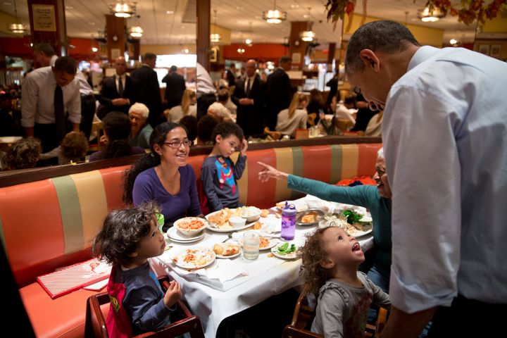 Looks like President Obama is interrupting dinner at Brooklyn's iconic restaurant Juniors. But this little girl doesn't mind.