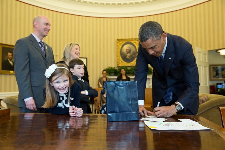 According to her big grin, watching the president sign an executive order is a lot of fun.
