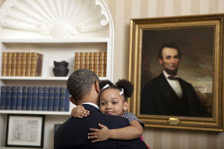 President Obama gets the biggest of hugs from an adorable girl with adorable pig tails in the White House.