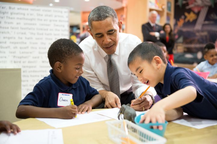 Students help Obama during a literacy lesson at an elementary school.