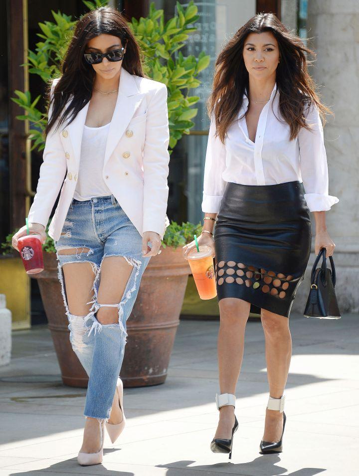 Kim rips the concrete runway in damaged jeans, alongside her big sis Kourtney.