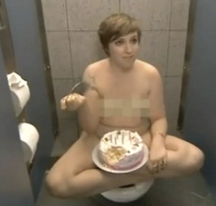 Dunham enjoys cake in a stall while rocking her birthday suit.