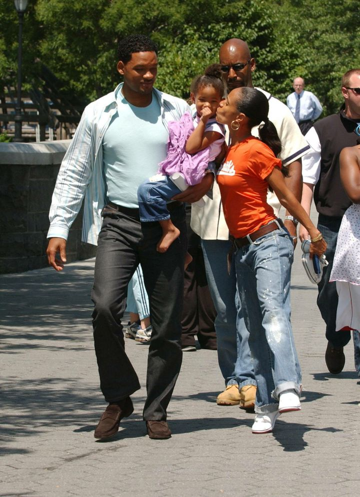 In another cute throwback moment, Jada smooches her daughter Willow while her husband holds her on his hip.