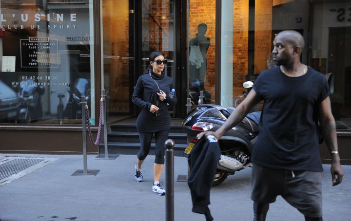 Kanye watches out for traffic as he and Kim cross the street.