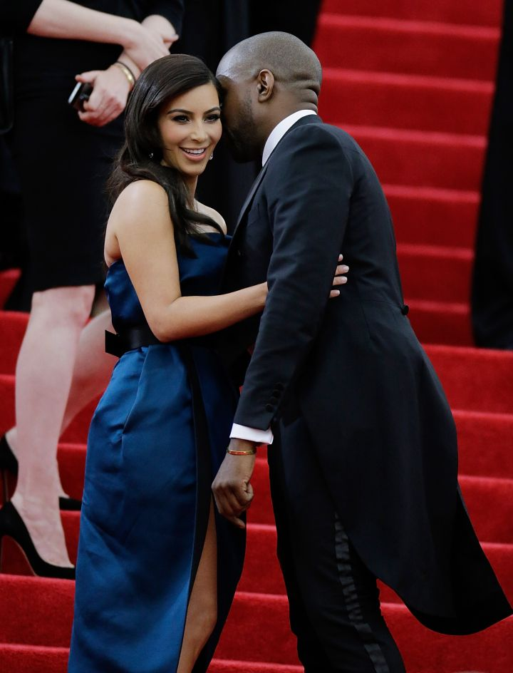 Kanye whispers into the ear of a smiling Kim Kardashian on the 2014 Met Gala red carpet.