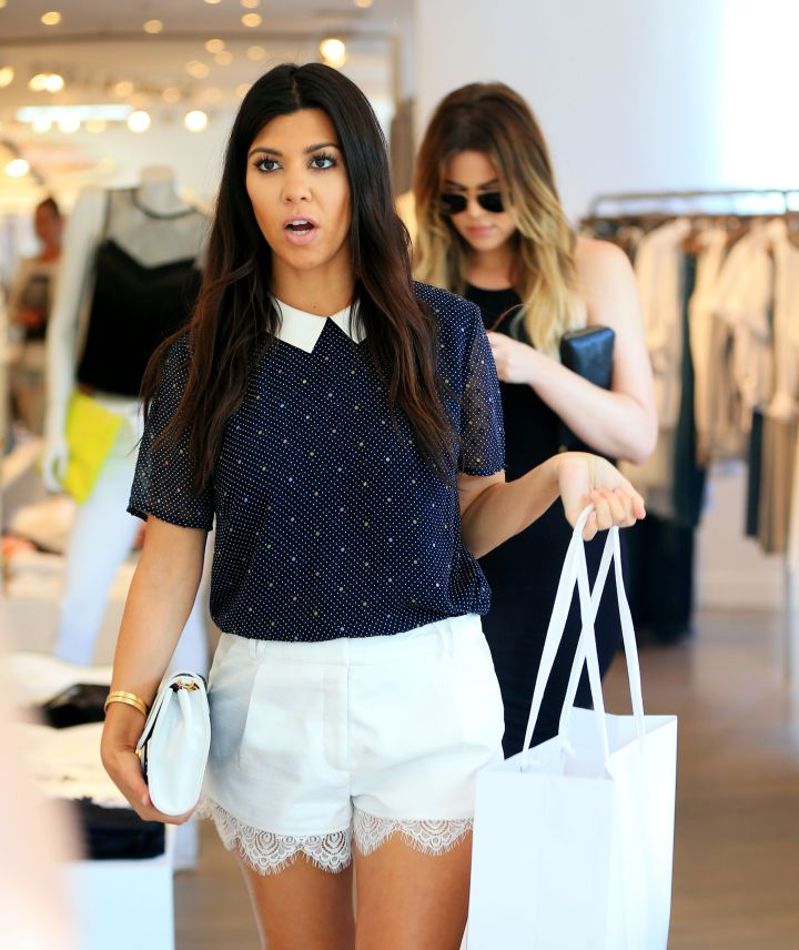 Newly pregnant Kourtney shops at Intermix in the Hamptons, while Khloe texts.