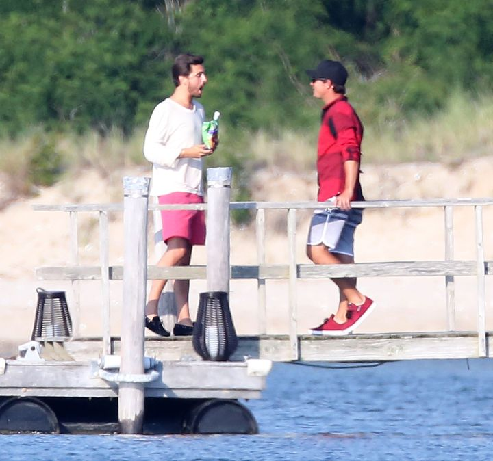 Scott Disick chows down on chips and drink while showing a friend the view from the pier of his house in the Hamptons, NY.