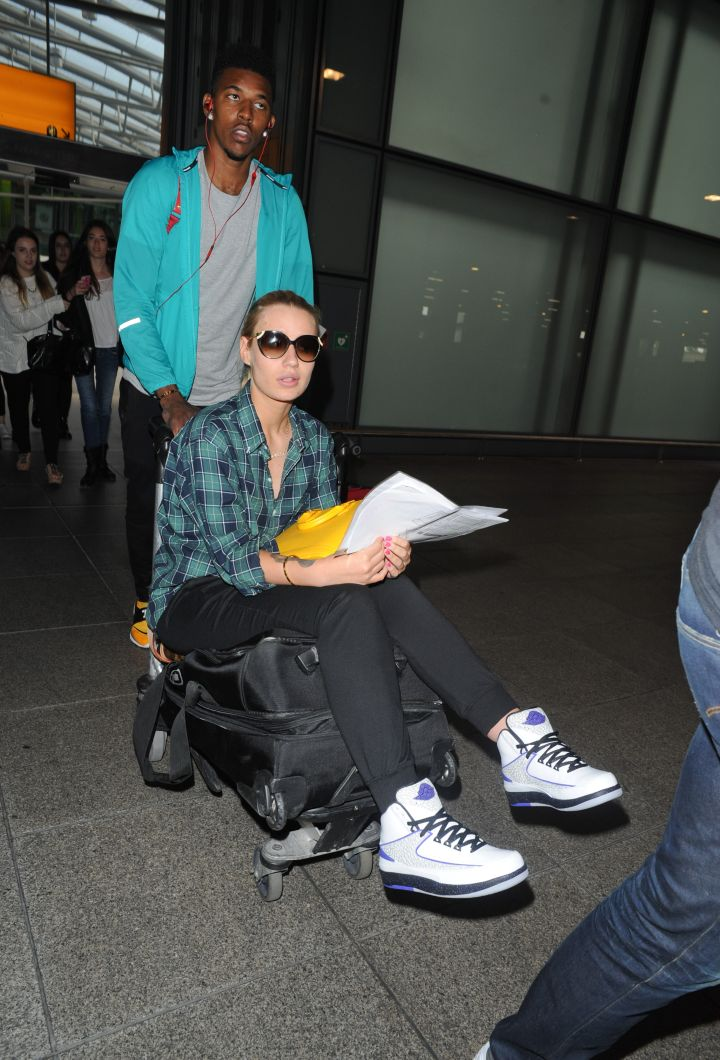 Iggy Azalea is helped by her beau Nick Young through Heathrow.