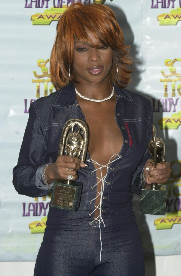 MJB shows some cleavage in a laced up denim top.