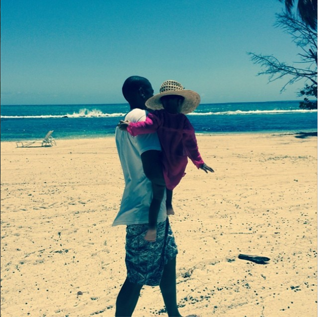 Blue rocked her sun hat while taking a stroll in the sand with her dad.