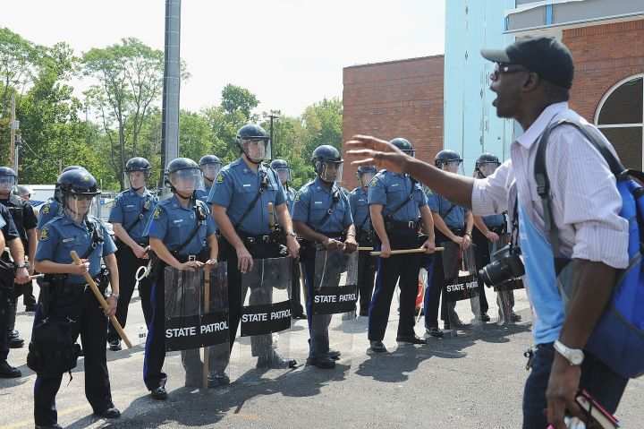 A man protests as a wall of police hold tight in Ferguson.