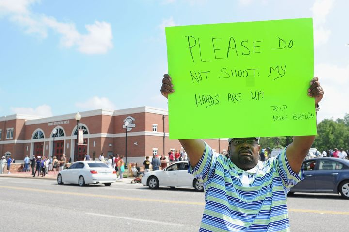 A man holds a sign in honor of Michael Brown, the unarmed teen who was killed by Ferguson police on Saturday, August 9, 2014.