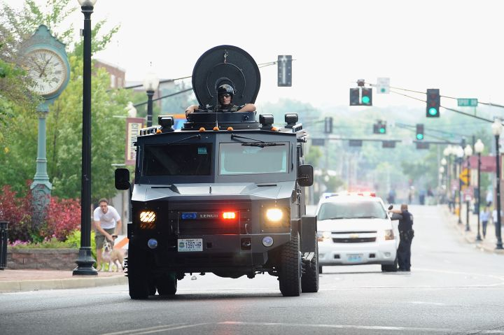 Police in a tactical vehicle travel down Ferguson streets to meet protestors.