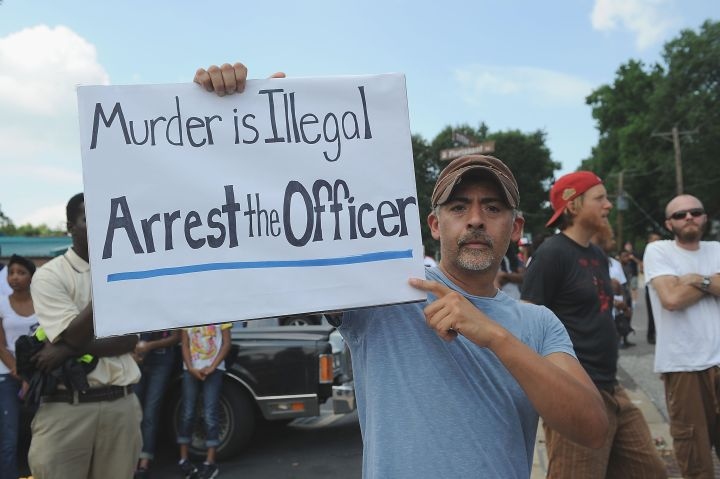 A protestor holds up a sign calling for the arrest of the officer who shot Michael Brown.