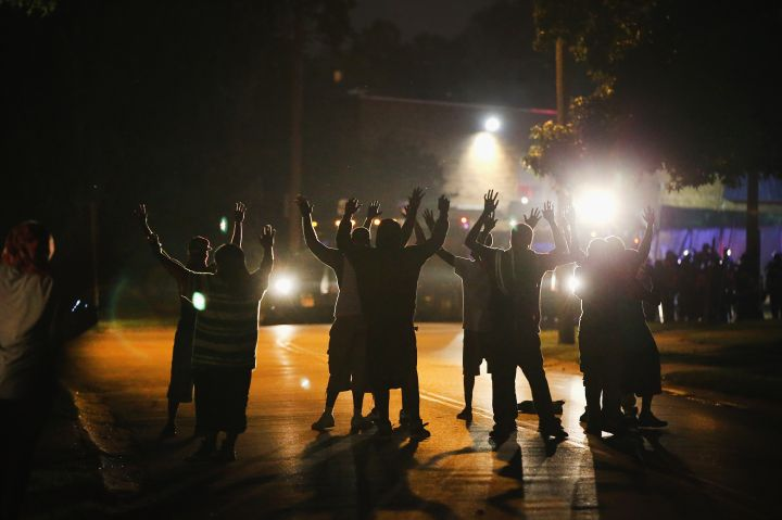 Protestors hold their hands high in the night sky to signify they are unarmed. Michael Brown was unarmed when he was shot by a Ferguson police officer.
