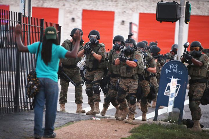 Police carrying rifles in riot gear approach a young unarmed man in Ferguson.
