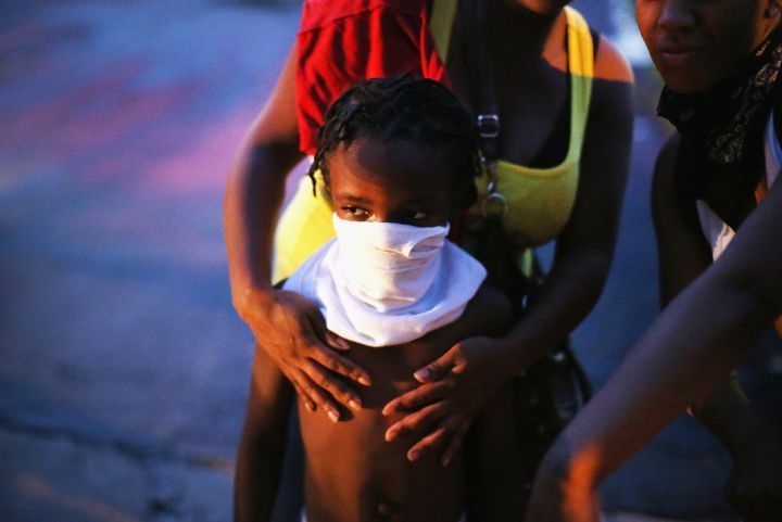 A child covers his face with a shirt after police fire tear gas into a crowd.