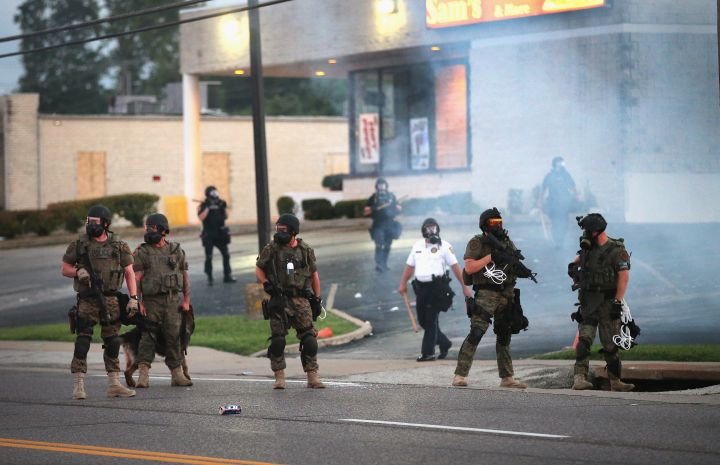 Officers stand guard after firing tear gas into the crowd.