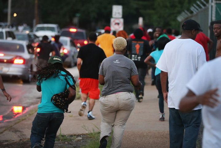 Residents flee after police fire tear gas into the crowd.