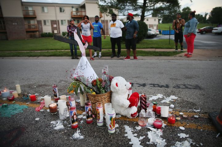 A memorial of candles, flowers and stuffed animals decorate the spot where Michael Brown was shot to death.