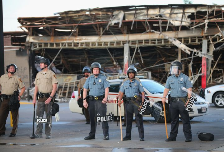Police in riot gear and sticks stand guard at a store destroyed in Ferguson riots.