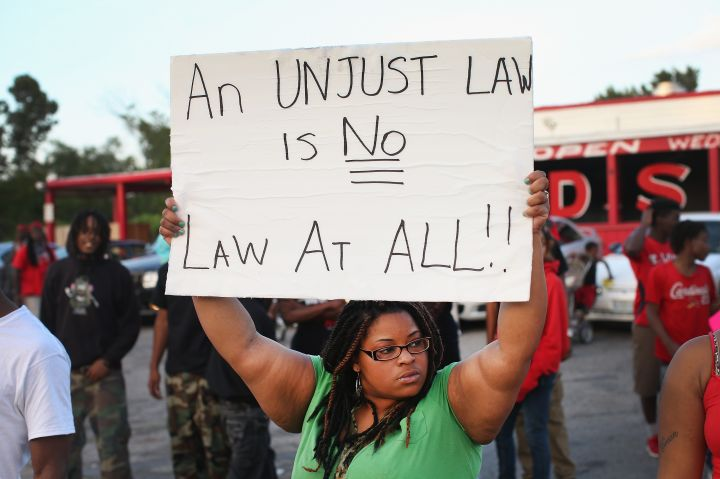 A woman holds a powerful sign.