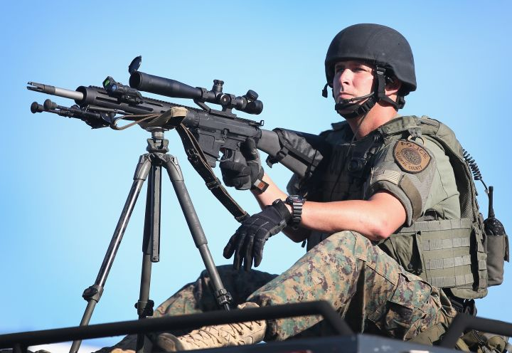 A sniper sits atop a vehicle in Ferguson.