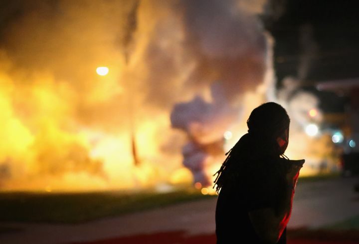 We lying? A resident of Ferguson watches as tear gas is released in the neighborhood.
