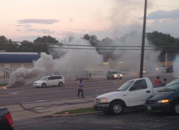St. Louis resident and reporter on the ground Antonio French stands in the middle of a cloud after police fire tear gas into the crowd.