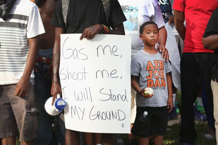 Demonstrator holds sign during a protest of the shooting of 18-year-old Mike Brown.