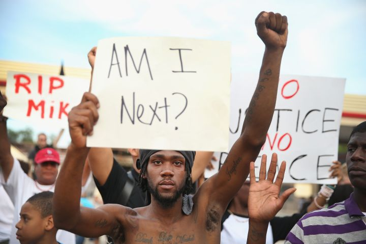 Demonstrator holds sign at protest of the Michael Brown shooting.