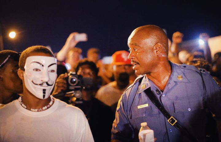 Capt. Ronald Johnson of the Missouri State Highway Patrol, who was appointed by the governor to take control of security operations in the city of Ferguson, walks with protesters.