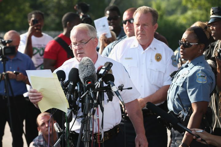 In the parking lot of a gas station, which was burned during rioting, Ferguson Police Chief Thomas Jackson announces the name of the officer who shot Michael Brown.