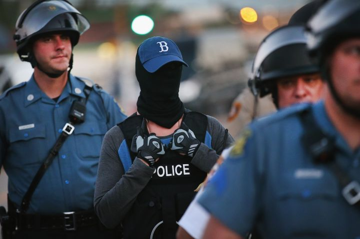 Police officer watches protest concealing his/her identity.
