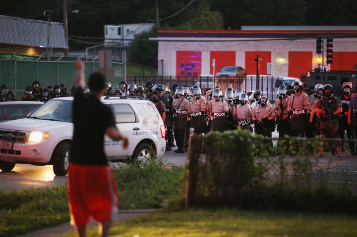 Police watch as demonstrators protest the shooting of unarmed teen Michael Brown.