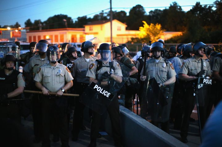 Ferguson police line up with riot gear where protesters are demonstrating.
