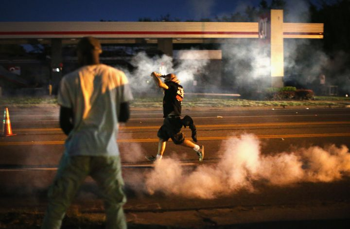 Ferguson police throw tear gas to disperse crowds protesting in the streets.