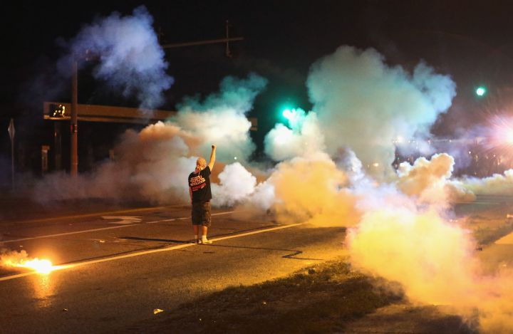 Protester stands his ground as police throw tear gas.