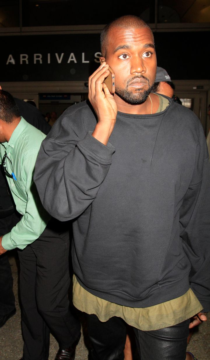 Kanye talks on the phone while arriving in LAX