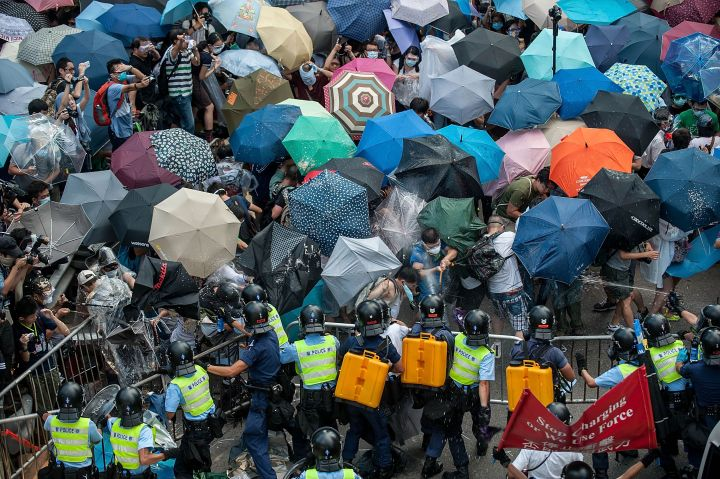 Demonstrators use umbrellas to protect themselves from tear gas during protests.