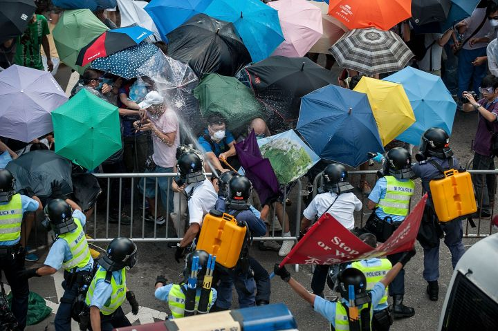 Protestors use umbrellas to shield them from tear gas.
